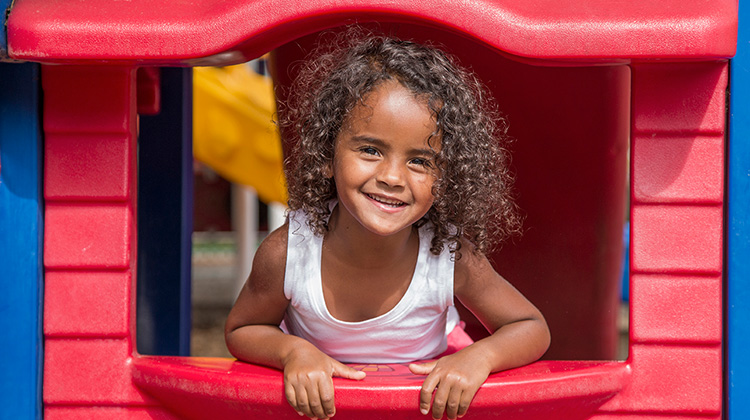 curly haired girl happily leaning out of playhouse
