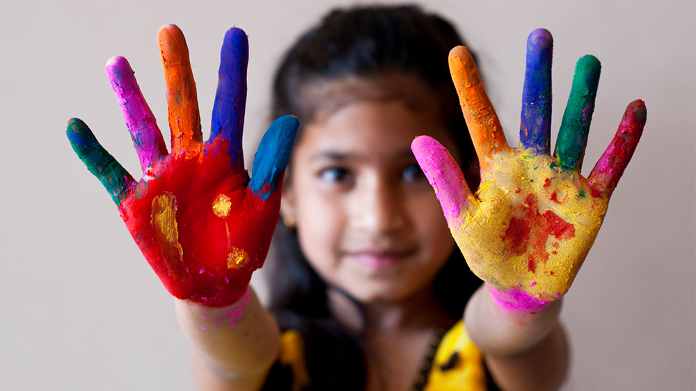 girl with outstretched hands with paint on her fingers and palms