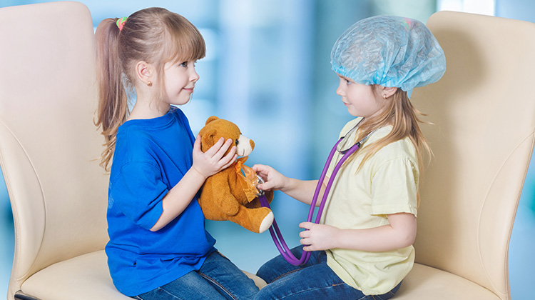 two girls playing doctor with a teddy bear