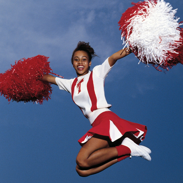 cheerleader in red and white uniform mid jump