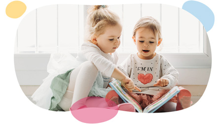 toddler sisters reading a book together