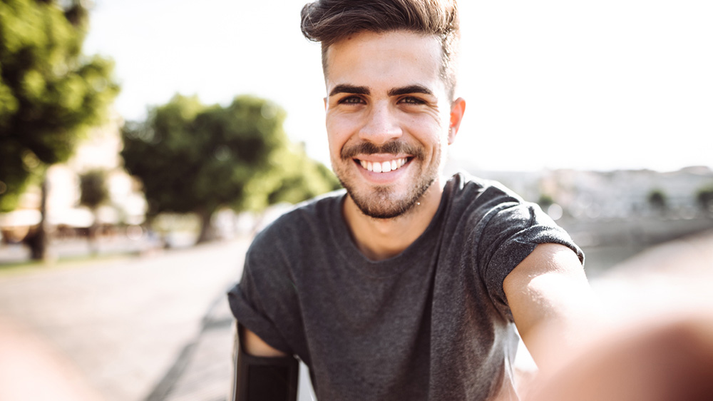 attractive young man smiling for a selfie