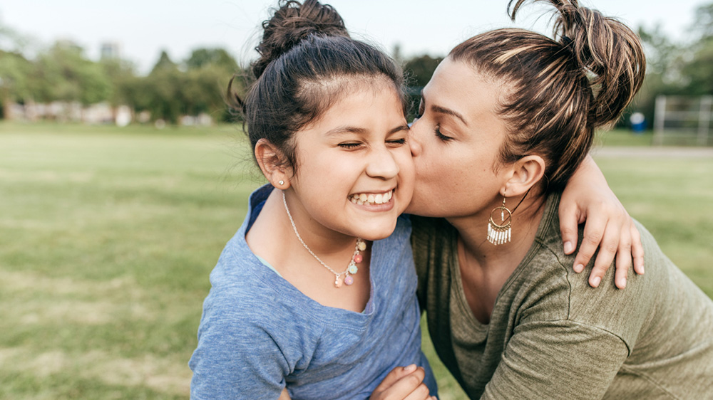 smiling girl being kissed on the cheek by her mother
