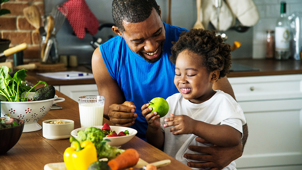 father and child enjoying fresh vegetables