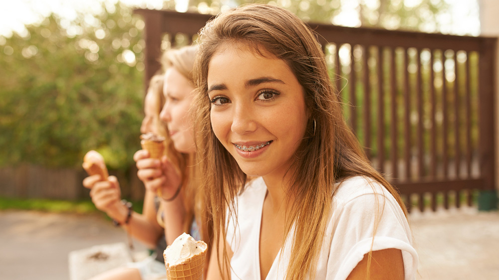 young girl eating ice cream with friends