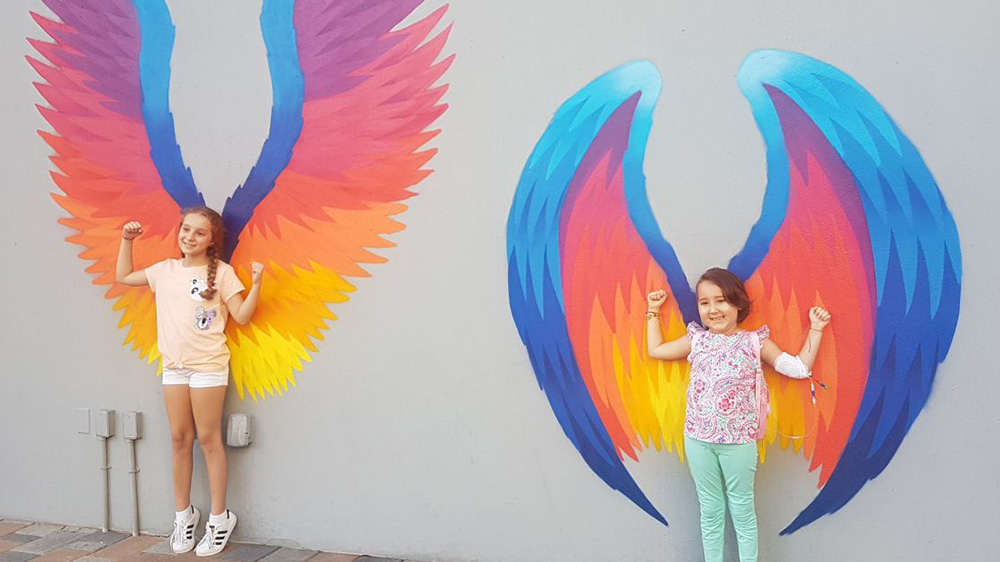former patient Isabella, and her sister, posing against a wall with multicolor angel wings