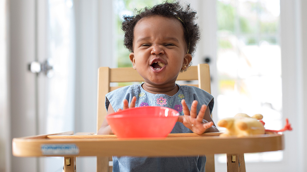 toddler girl eating on a high chair