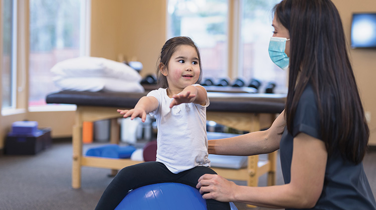 little girl sitting on exercise ball during rehab exercises with therapist