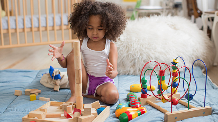 curly haired girl playing with wood blocks