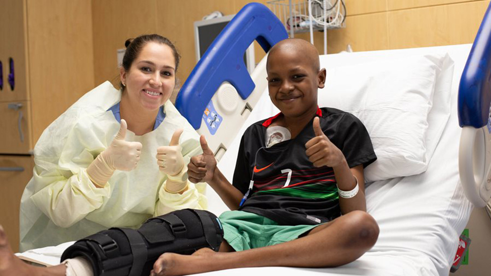 former patient Tyler with his nurse, giving the thumbs up after surgery