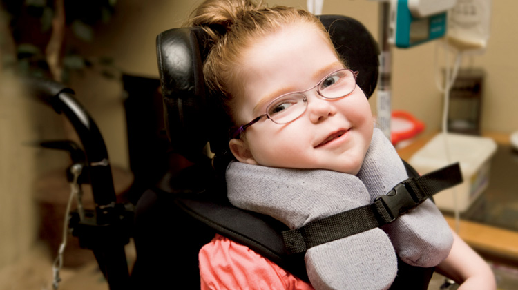 girl in neck brace and special wheelchair
