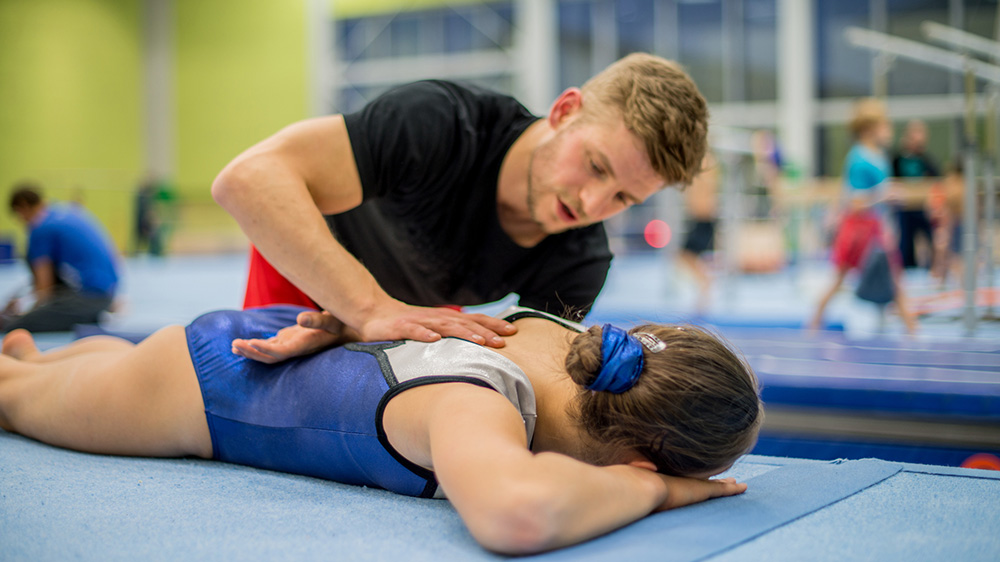 ATC performing stretching exercise on gymnast