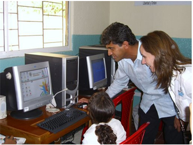Dr. Narendra Kini, President and CEO of Miami Children's Hospital, and Dr. Maria Franco, Cystic Fibrosis Center Director of Miami Children's Hospital, teach a young girl how to navigate one of the 140 computers donated to the Cartagena, Colombia school system.